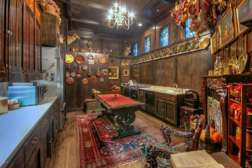 <p>The kitchen island is a repurposed 1800s library table, but the amenities are all modern, including two stoves, a dishwasher and a large fridge. On the right side of the photograph, under the paintings, is a fireplace, one of two in the house.</p>