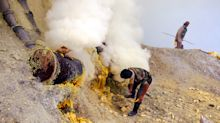 Workmen mining sulfur from a live volcano