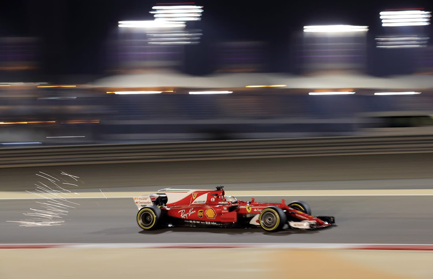 <p>Sparks fly off the car of Ferrari driver Sebastian Vettel of Germany during the second practice session for the Bahrain Formula One Grand Prix, at the Formula One Bahrain International Circuit in Sakhir, Bahrain, April 14, 2017. The Bahrain Formula One Grand Prix will take place on Sunday. (Photo: Hassan Ammar/AP) </p>