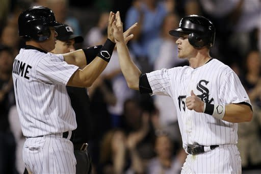 Chicago White Sox's Kosuke Fukudome, left, and Gordon Beckham celebrate after scoring on a single by Alejandro De Aza off Cleveland Indians starting pitcher Justin Masterson during the fifth inning of a baseball game, Thursday, May 3, 2012, in Chicago. (AP Photo/Charles Rex Arbogast)