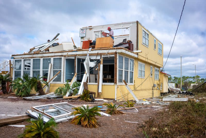 JJ McNelis tries to recover some items from his building after Hurricane Sally swept through, at Perdido Key, Florida