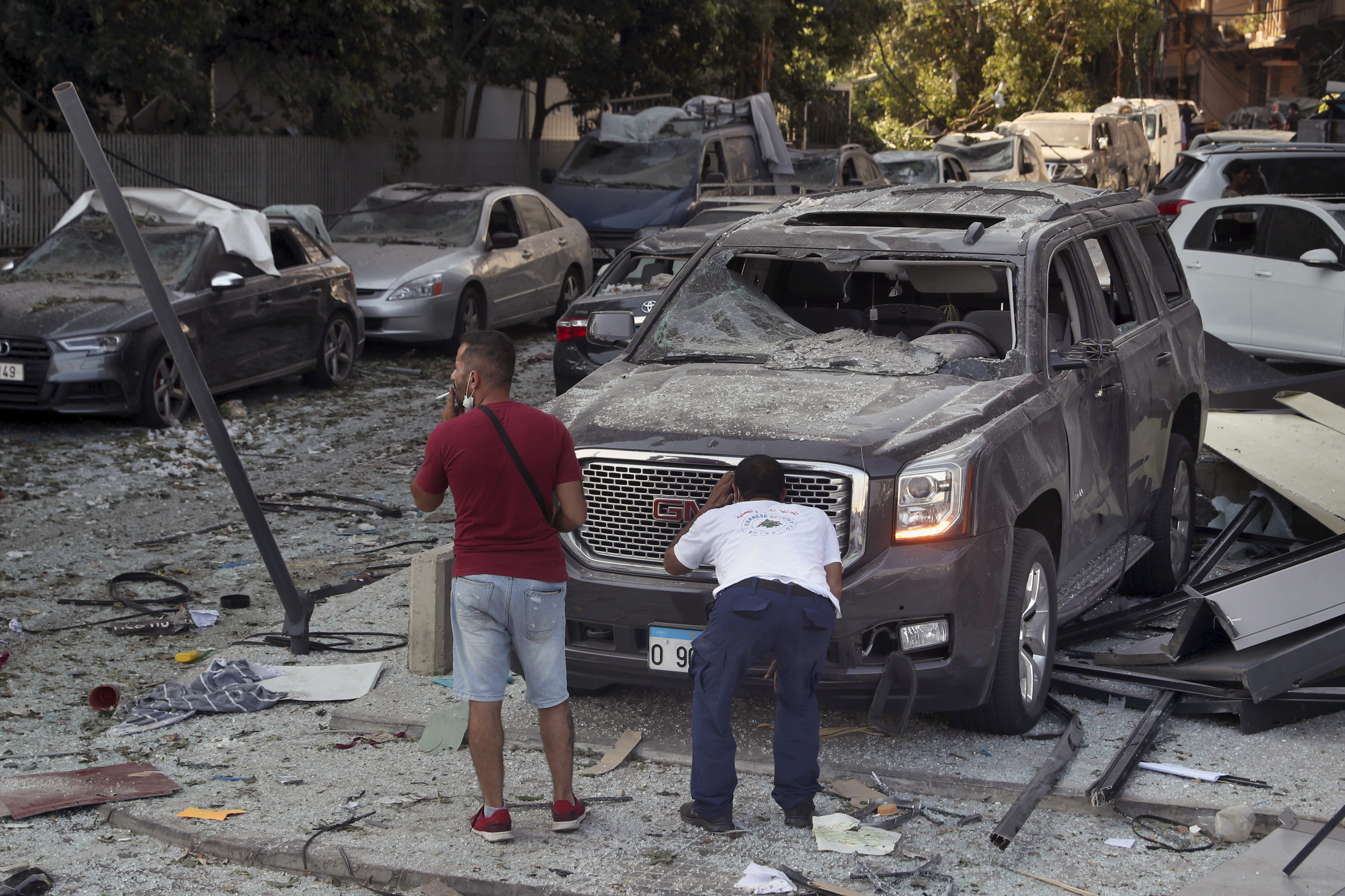 A man inspects his a damaged car after a massive explosion on Tuesday, in Beirut, Lebanon, Wednesday, Aug. 5, 2020. The explosion flattened much of a port and damaged buildings across Beirut, sending a giant mushroom cloud into the sky. In addition to those who died, more than 3,000 other people were injured, with bodies buried in the rubble, officials said. (AP Photo/Bilal Hussein)