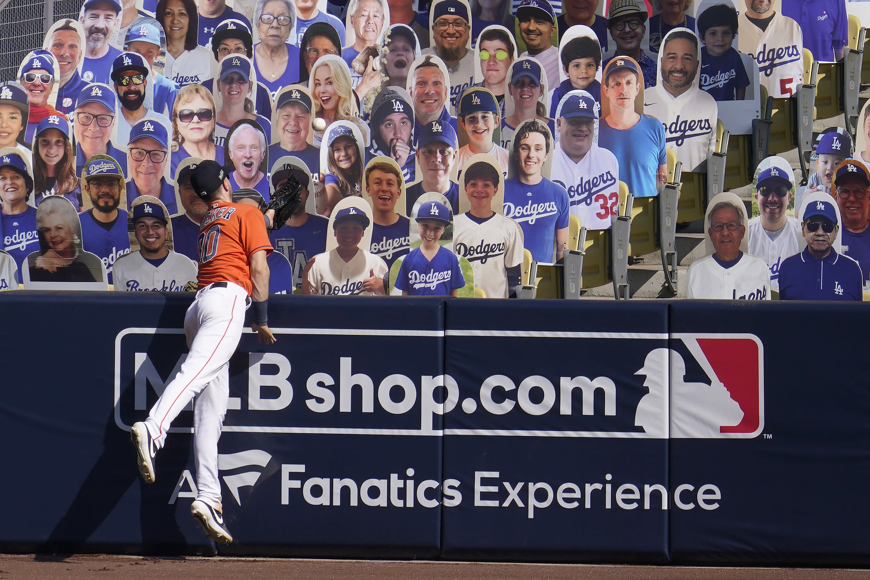 Houston Astros right fielder Kyle Tucker cannot catch a three-run home run hit by Oakland Athletics' Chad Pinder that lands in front of cutouts seated at Dodger Stadium during the seventh inning of Game 3 of a baseball American League Division Series in Los Angeles, Wednesday, Oct. 7, 2020. (AP Photo/Marcio Jose Sanchez)