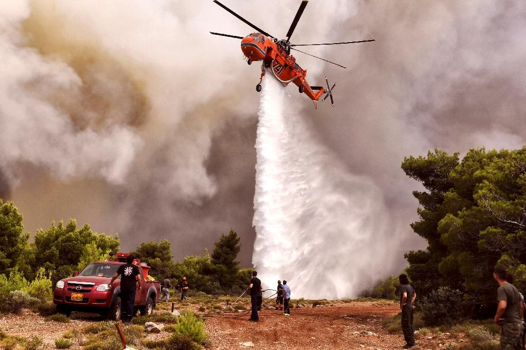 A firefighting helicopter drops water to extinguish flames during a wildfire at the village of Kineta, near Athens, on July 24 (AFP Photo/Valerie GACHE)
