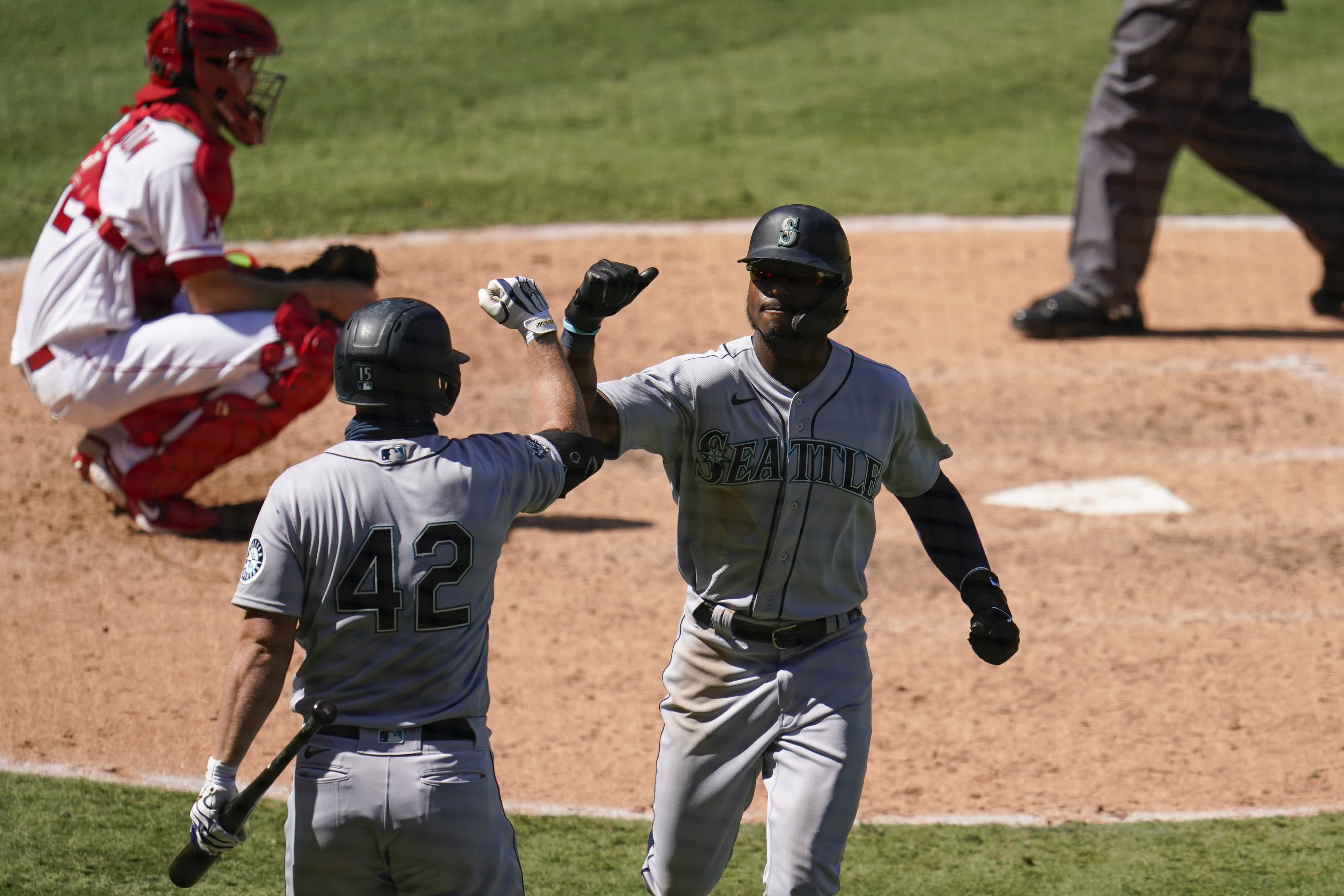Seattle Mariners' Kyle Lewis, right, celebrates his solo home run with Kyle Seager during the seventh inning of a baseball game against the Los Angeles Angels Sunday, Aug. 30, 2020, in Anaheim, Calif. (AP Photo/Marcio Jose Sanchez)