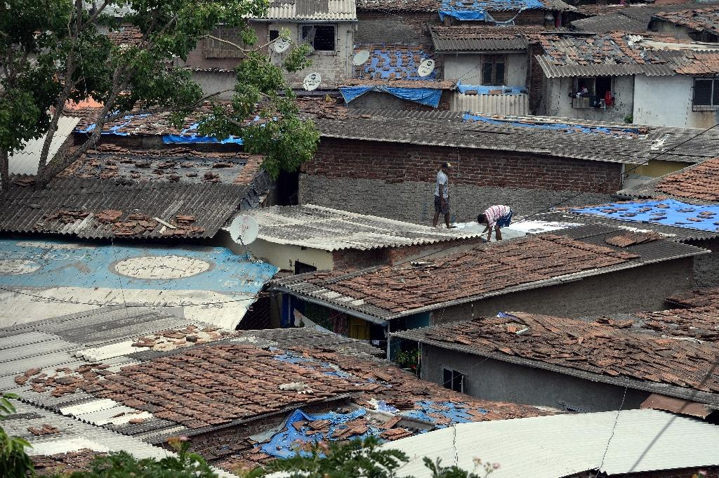 Indian men repair the asbestos roof of their home in a slum where the majority of houses have asbestos roofs in Mumbai, June 6, 2015 (AFP Photo/Indranil Mukherjee)