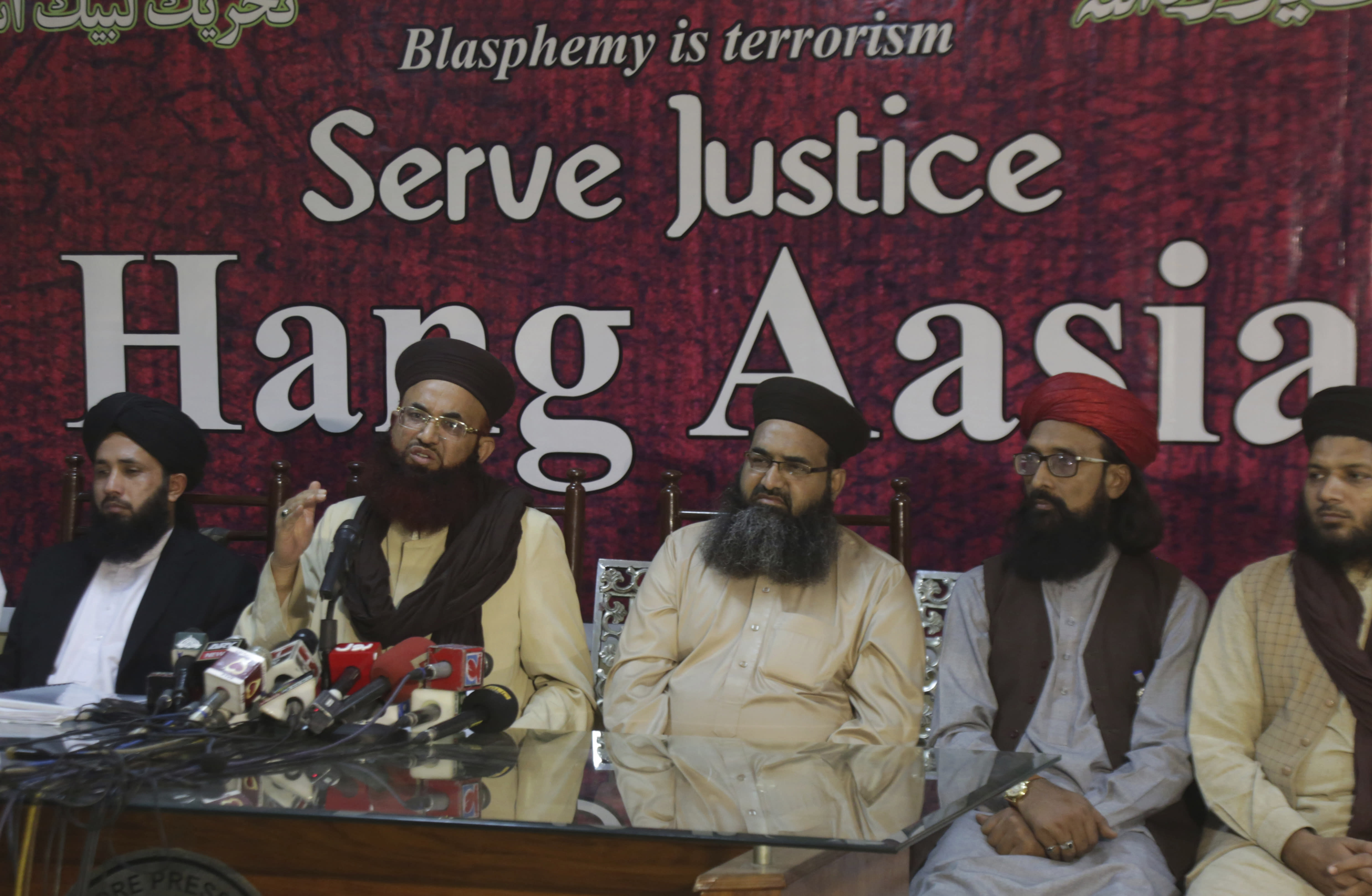 Ashraf Asim Jalali, second from left, leader of Pakistani Tehreek-e-Labbaik religious Party addresses a news conference with others regarding the acquittal of Christian woman Asia Bibi, in Lahore, Pakistan, Thursday, Nov. 8, 2018. A Christian woman acquitted after eight years on death row in Pakistan for blasphemy was released but her whereabouts in Islamabad on Thursday remained a closely guarded secret in the wake of demands by radical Islamists that she be publicly executed. (AP Photo/K.M. Chaudary)