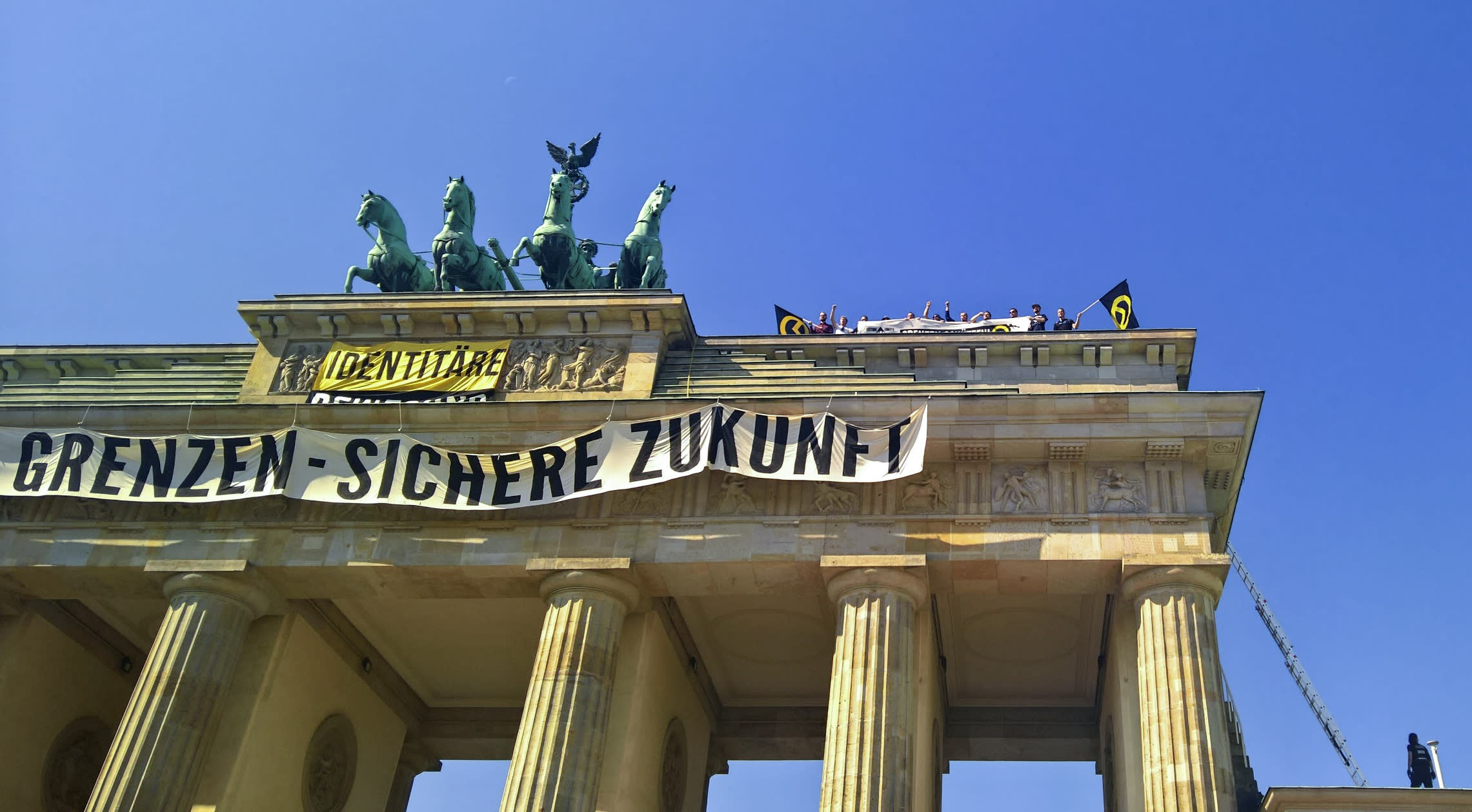 Activists of the Identitarian Movement protest on the Brandenburg Gate with a banner reading 'secure borders - secure fututre'Saturday, Aug. 27, 2016.The German domestic intelligence agency says it is stepping up observation of the far-right Identitarian Movement in Germany that campaigns against immigrants and Islam. (AP Photo/Frank Jordans)