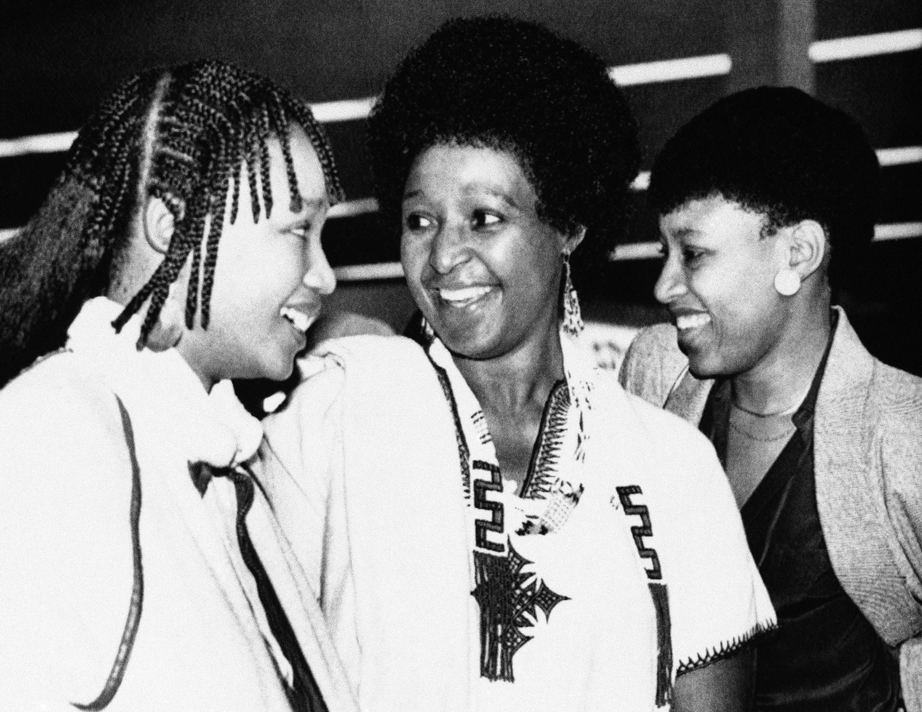 <p>Winnie Mandela, with daughters Dlamini, left, and Zinzi, right, arrives at Cape Town's airport on Sept. 11, 1985, on her way to visit her imprisoned husband, anti-apartheid activist Nelson Mandela. (Photo: Greg English/AP) </p>