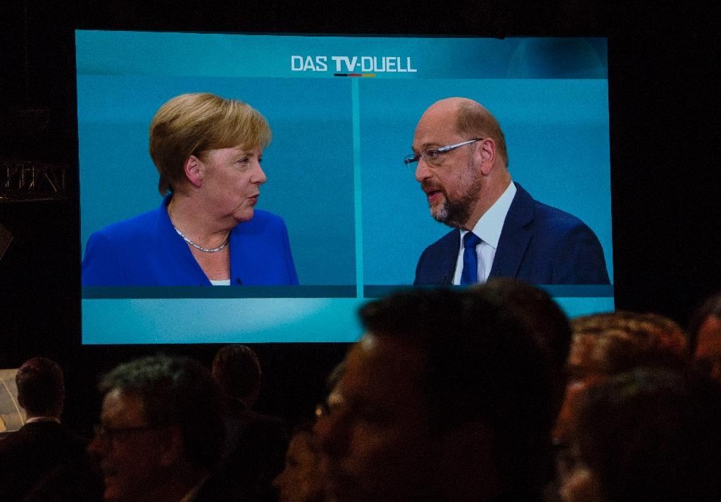 Journalists watch a televised debate between Angela Merkel and Martin Schulz at a television studio in Berlin on September 3, 2017
