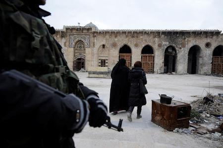 A Syrian army soldier stands guard as visitors walk inside Aleppo's Umayyad mosque, Syria January 31, 2017. REUTERS/Omar Sanadiki