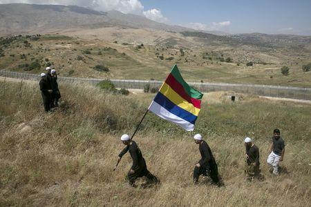 Members of the Druze community walk next to the border fence between Syria and the Israeli-occupied Golan Heights near the Druze village of Majdal Shams