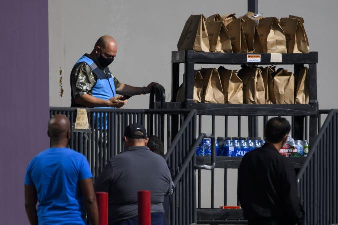 An Amazon.com Inc. delivery driver pushes a cart of groceries to load into a vehicle outside of a distribution facility on February 2, 2021 in Redondo Beach, California. - Jeff Bezos said February 1, 2021, he would give up his role as chief executive of Amazon later this year as the tech and e-commerce giant reported a surge in profit and revenue in the holiday quarter. The announcement came as Amazon reported a blowout holiday quarter with profits more than doubling to $7.2 billion and revenue jumping 44 percent to $125.6 billion. (Photo by Patrick T. FALLON / AFP) (Photo by PATRICK T. FALLON/AFP via Getty Images)