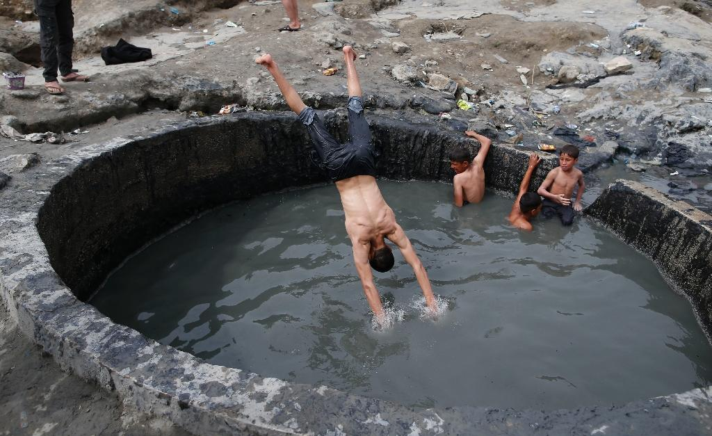 Iraqis bathe in a sulphur pond in Hamam al-Alil, about 14 kilometres (almost nine miles) from the southern outskirts of Mosul, on April 1, 2017 (AFP Photo/AHMAD GHARABLI)