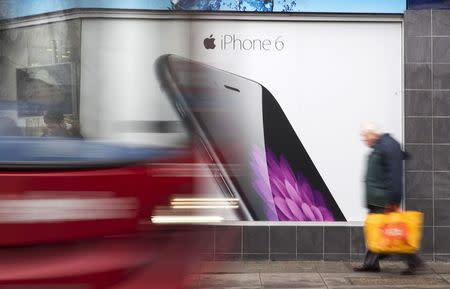 A bus and pedestrian pass an advertisement for the Apple iPhone 6 in north London