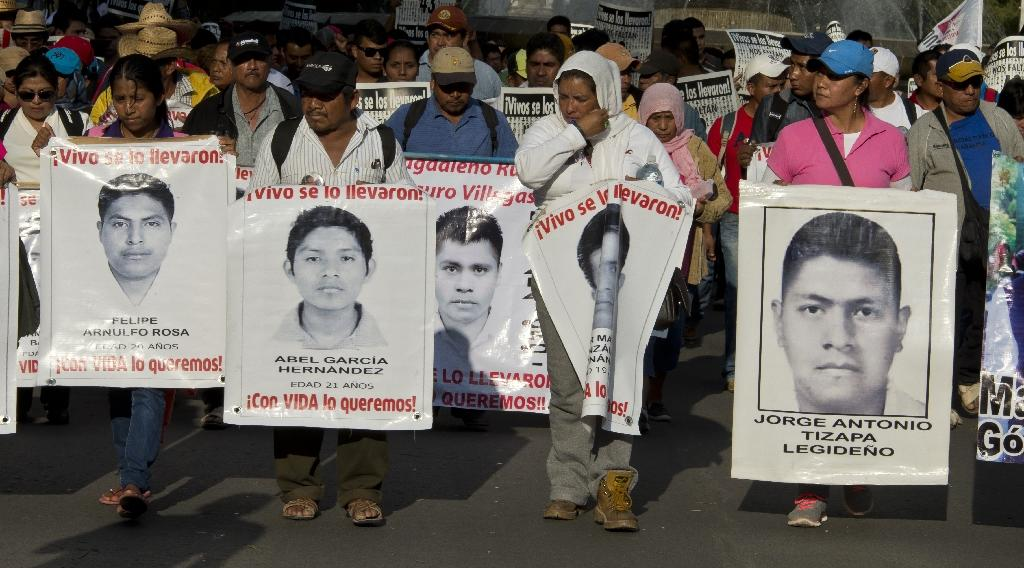 Relatives of the 43 missing students from Ayotzinapa hold their portraits during a march commemorating five months after their disappearance, February 26, 2015, in Mexico City (AFP Photo/Omar Torres)