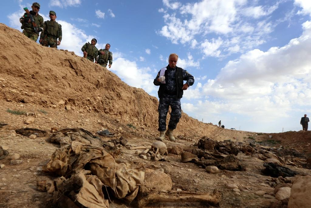 Members of the Kurdish forces look at the remains of Yazidis killed by the Islamic State (IS) jihadist group, in February 2015, after discovering a mass grave near the Iraqi village of Sinuni (AFP Photo/Safin Hamed)
