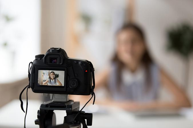 Professional camera shooting young smiling female tutor or coach making presentation or recording master class tutorial for channel, woman business vlogger filming video training for blog or website