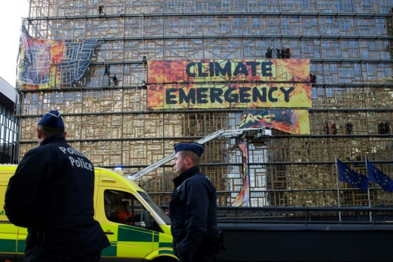 Before the European summit could even begin, police and firefighters were forced to intervene to dislodge Greenpeace protesters who scaled the side of the main venue (AFP Photo/Aris Oikonomou)