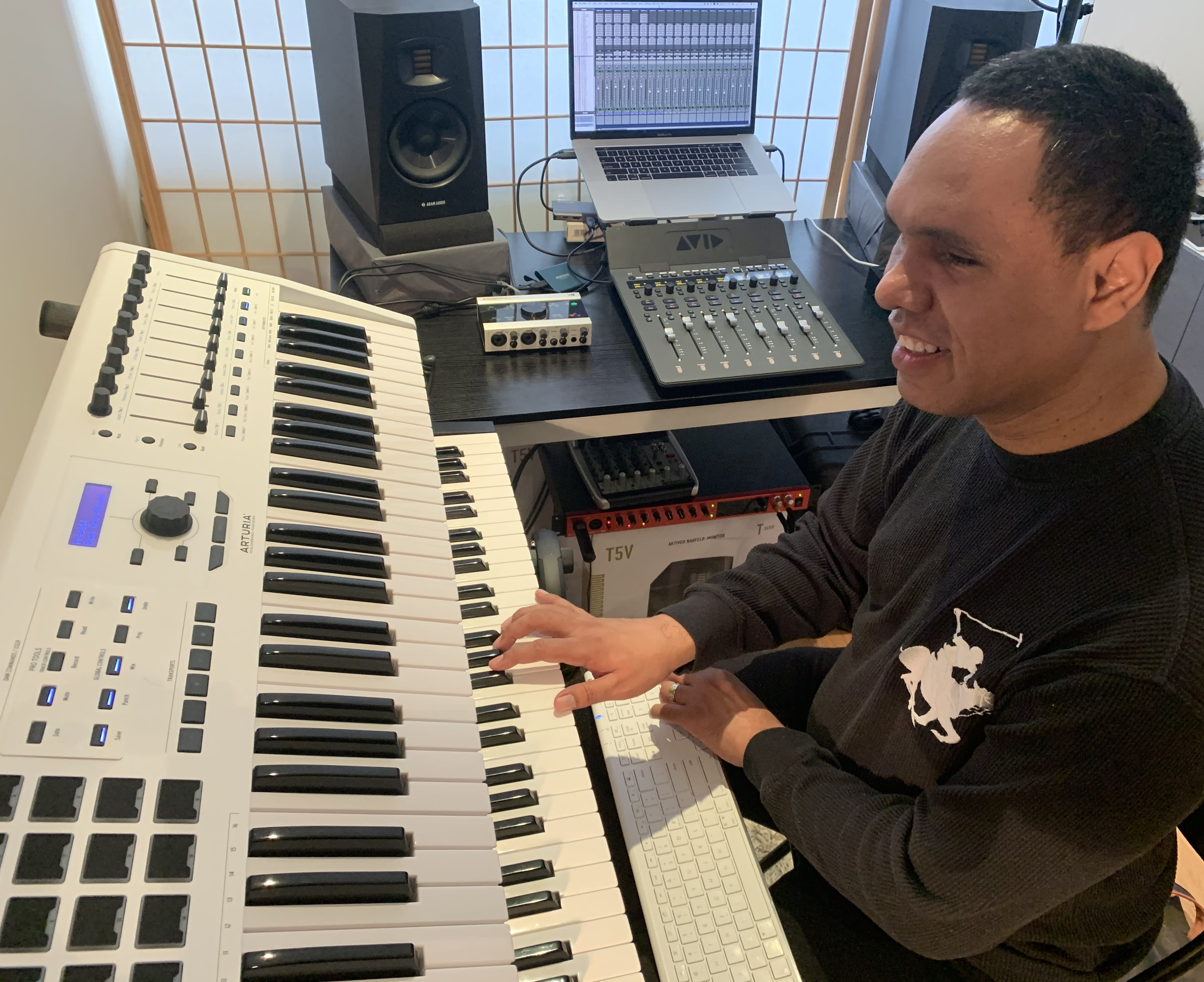 Visually impaired audio engineer Jason Dasent sits in a studio, with his right hand on a keyboard in front of him.