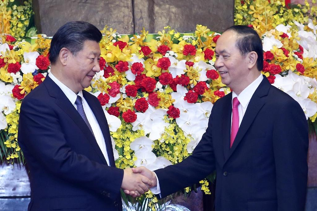 Chinese President Xi Jinping (L) shakes hands with Vietnamese President Tran Dai Quang (R) at the presidential palace in Hanoi