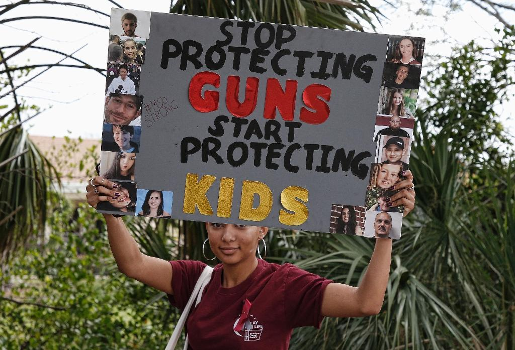 A student holds a sign during a protest against gun violence at Coral Glades High School in Florida (AFP Photo/RHONA WISE)