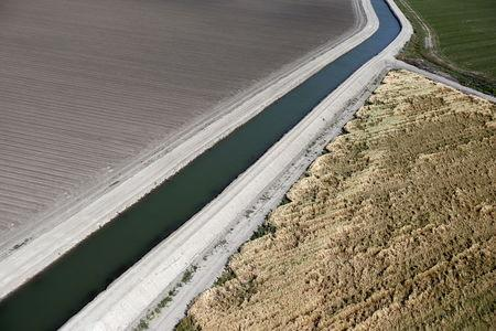 A canal runs through farm fields in Los Banos, California, United States May 5, 2015. REUTERS/Lucy Nicholson