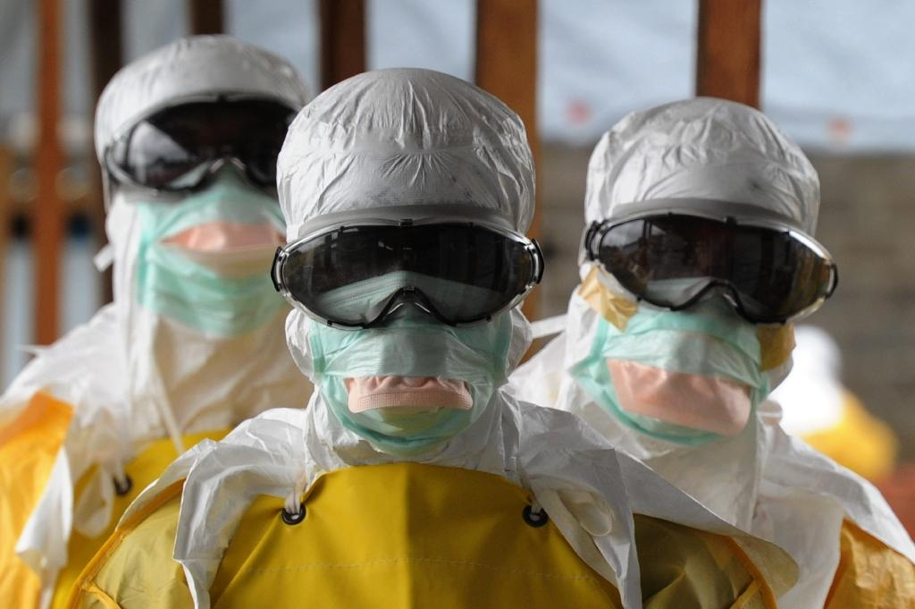 Health care workers wearing protective suits leave a high-risk area at the Elwa hospital in Monrovia on August 30, 2014