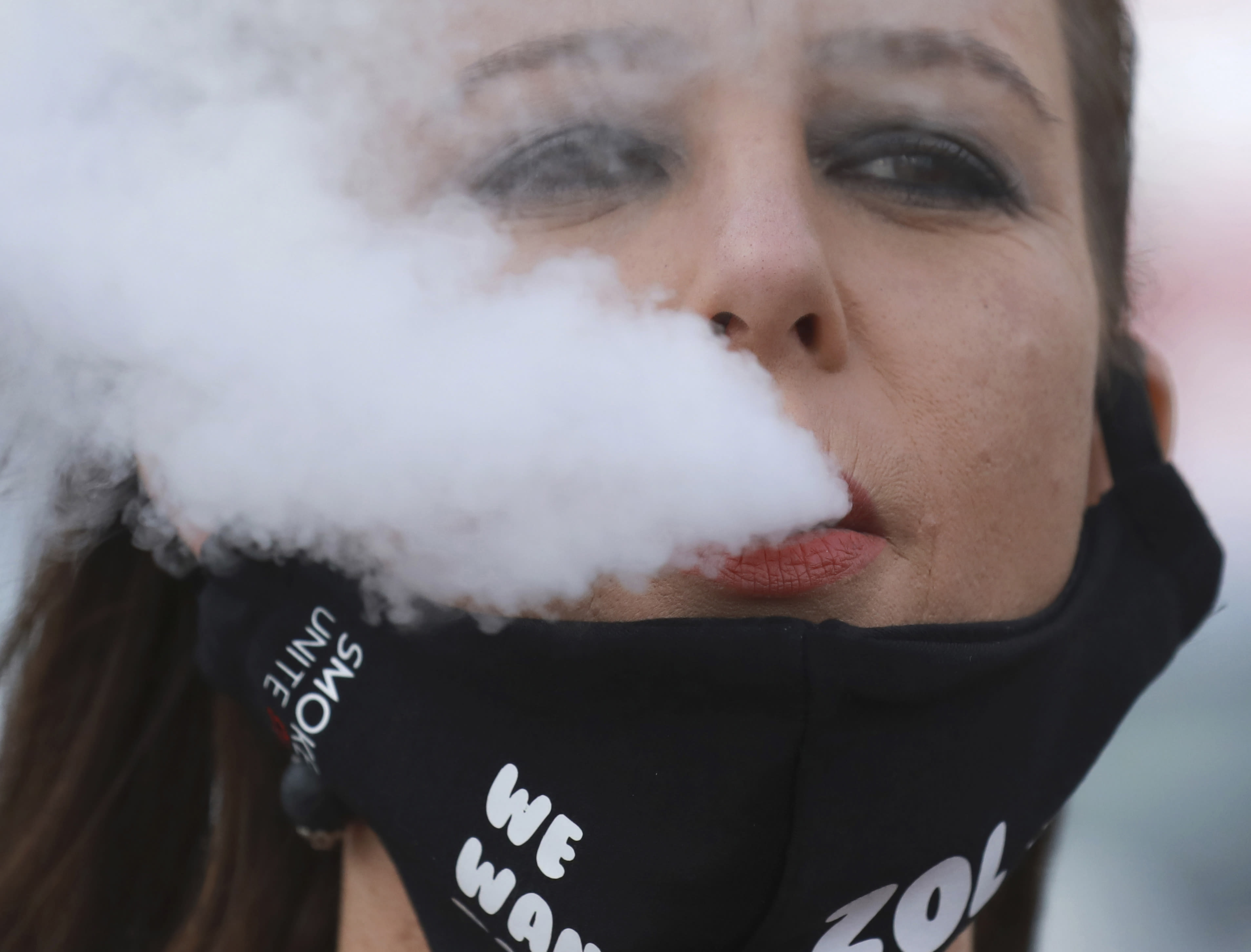 FILE — In this June 2, 2020 file photo, a demonstrator exhales smoke during a protest against the tobacco ban outside parliament in Cape Town, South Africa. South Africa is three months into a ban on the sale of cigarettes and other tobacco products, an unusual tactic employed by a government to protect the health of its citizens during the coronavirus pandemic. The country is one of just a few around the world to have banned tobacco sales during the pandemic and the only one to still have it in place. (AP Photo/Nardus Engelbrecht/File)