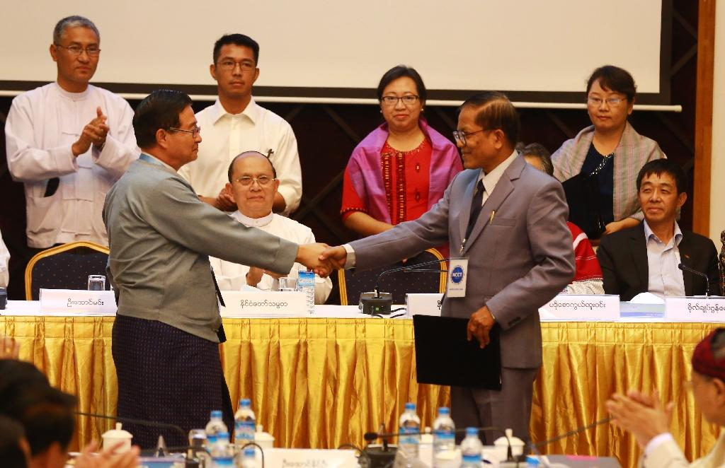Myanmar President Thein Sein (C) looks on as Aung Min (L), of the Union Peace Working Comittee (UPWC), shakes hands with Naing Han Tha (R), of the Nationwide Ceasefire Coordinating Team (NCCT), in a ceasefire draft agreement in Yangon, March 31, 2015 (AFP Photo/)