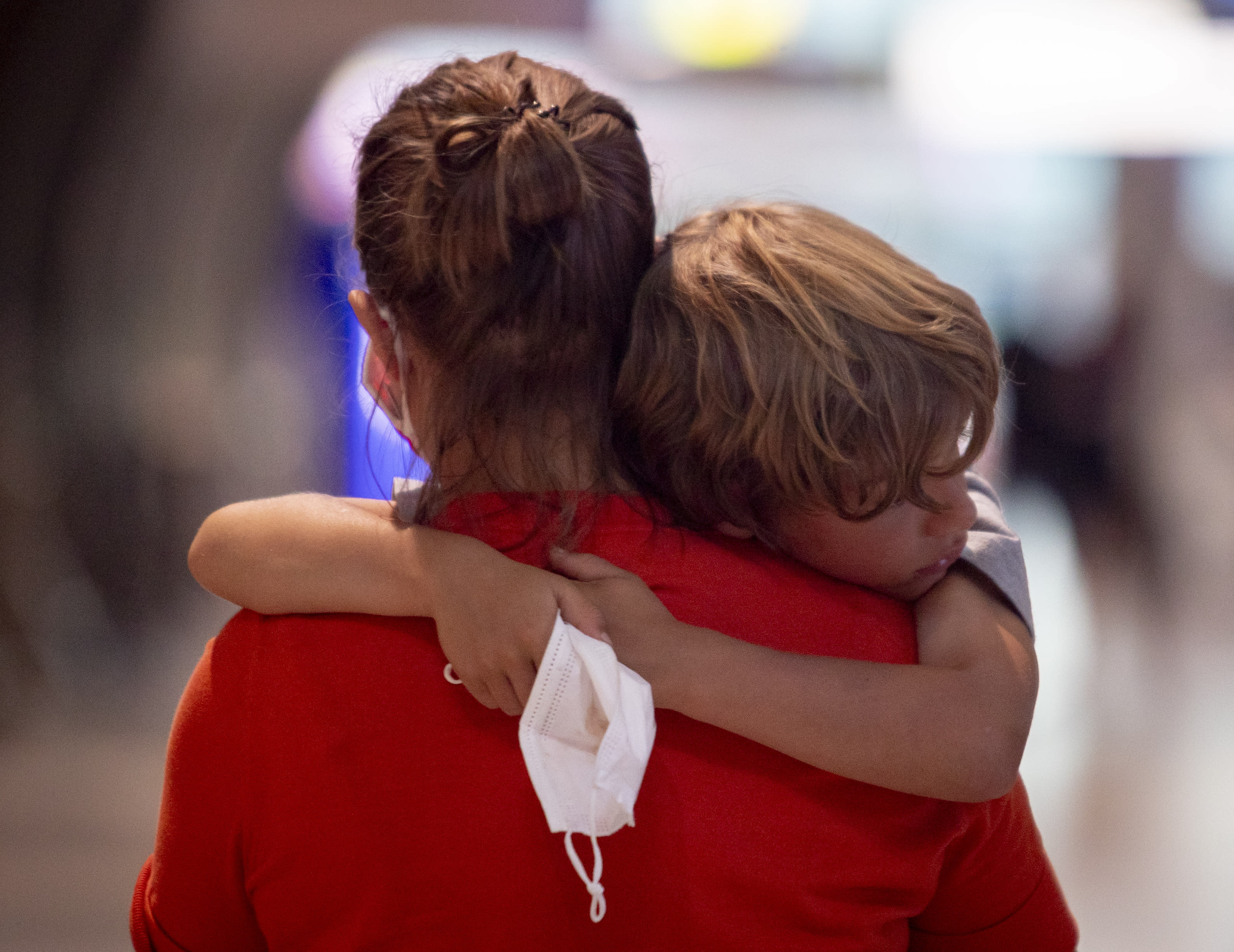 A tired boy is carried by his mother at the airport in Frankfurt, Germany, Saturday, Aug. 8, 2020. From Saturday on Covid-19 tests are mandatory for passengers coming from a high-risk-country. (AP Photo/Michael Probst)