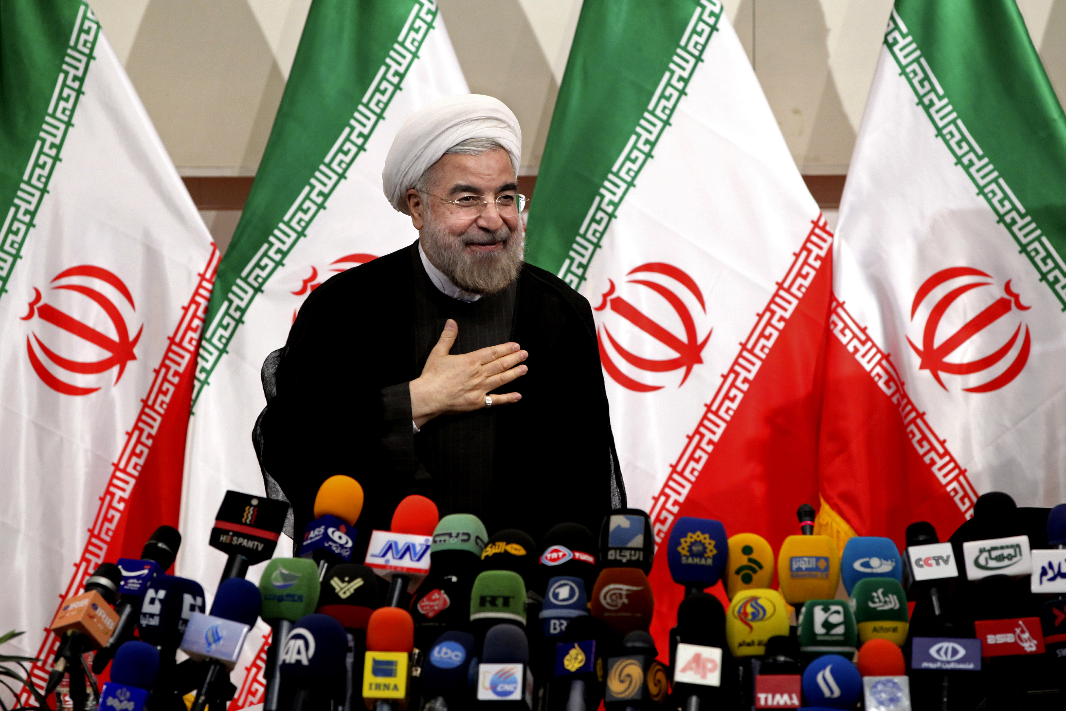 "Iranian newly elected President Hasan Rowhani, places his hand on his heart as a sign of respect, after speaking at a press conference, in Tehran, Iran, Monday, June 17, 2013. Rowhani showcases his reformist image by promising a ""path of moderation,"" the easing of nuclear tensions and steps to narrow the huge divide with the United States. He also make clear where he won't go, saying he opposes any halt to uranium enrichment, at the heart of the nuclear standoff. (AP Photo/Ebrahim Noroozi)"
