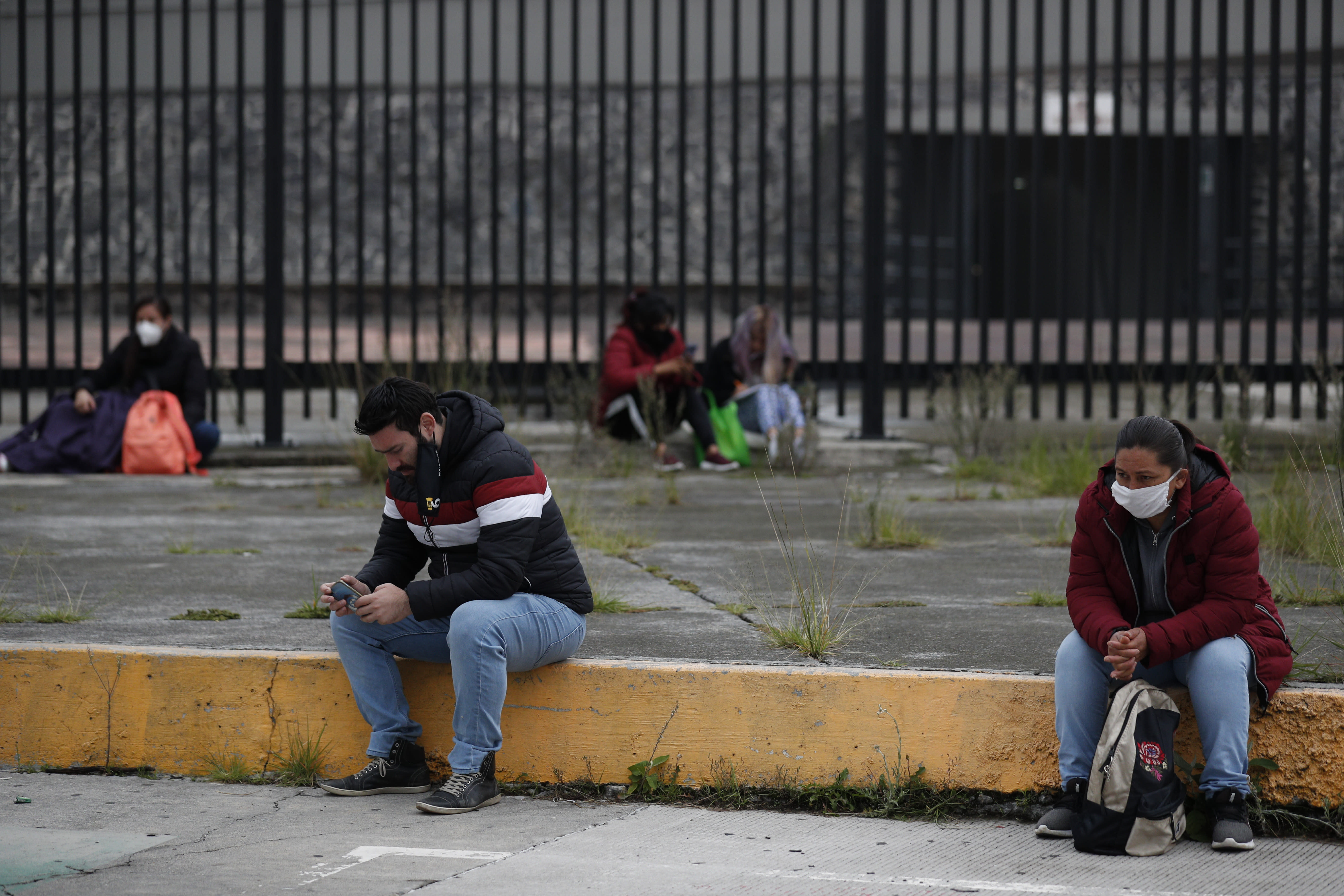People wait outside University Olympic Stadium as their family members take the entrance exam for Mexico's National Autonomous University inside the stadium amidst the ongoing coronavirus pandemic in Mexico City, Wednesday, Aug. 19, 2020. More than 2,000 hopefuls registered to take the exam at the stadium, where it was being offered for the first time, and more than 80,000 aspirants were registered nationwide to take the exam. (AP Photo/Rebecca Blackwell)