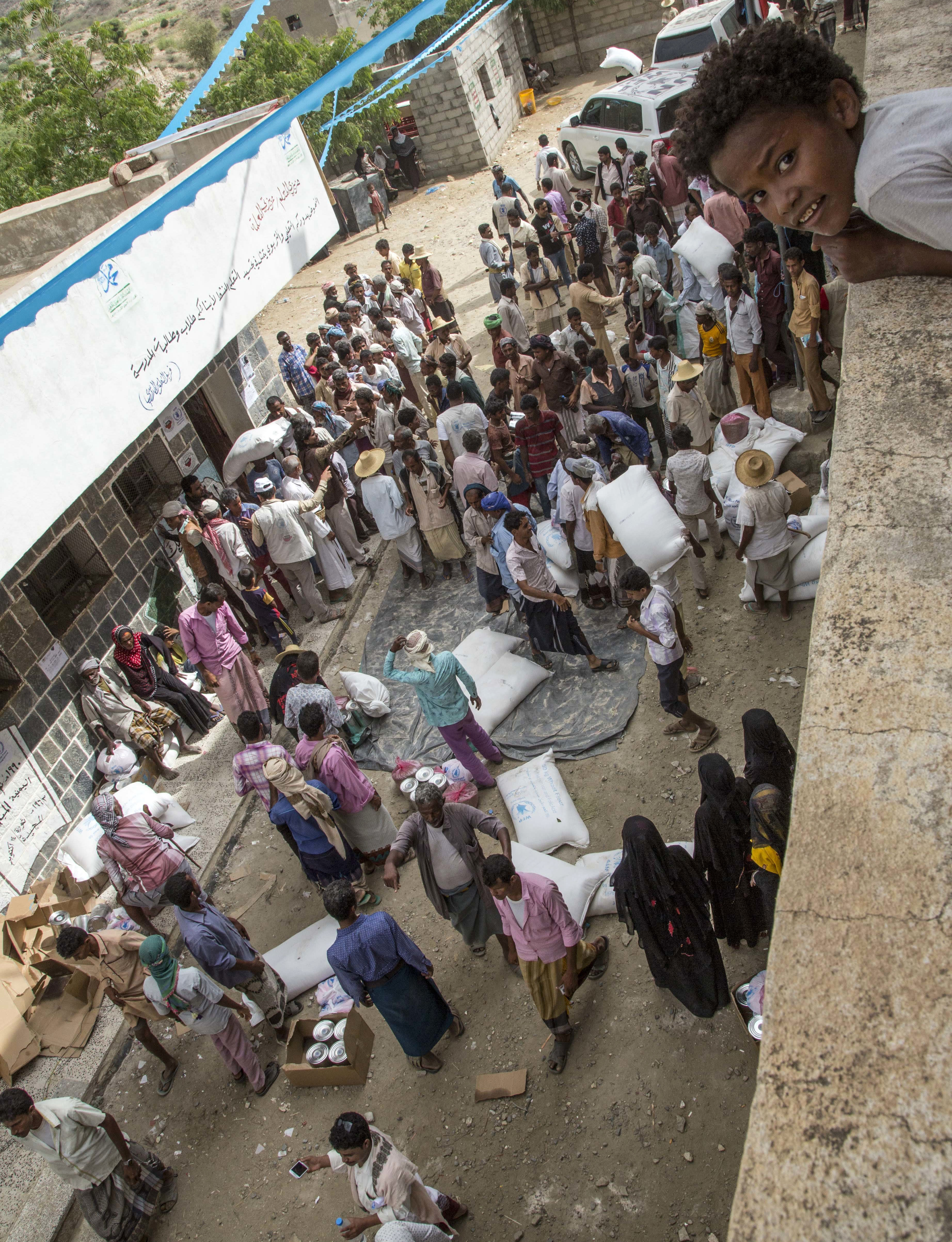 """This Nov. 16, 2018 photo shows food distribution by the WFP in Aslem, Yemen. The U.N. food agency said Thursday, Dec. 6, 2018 it is planning to rapidly scale up food distribution to help another 4 million people in Yemen over the next two months, more than a 50-percent increase in the number reached now, if access can be maintained in the poor, war-stricken country"""". (Marco Frattini/WFP via AP)"""
