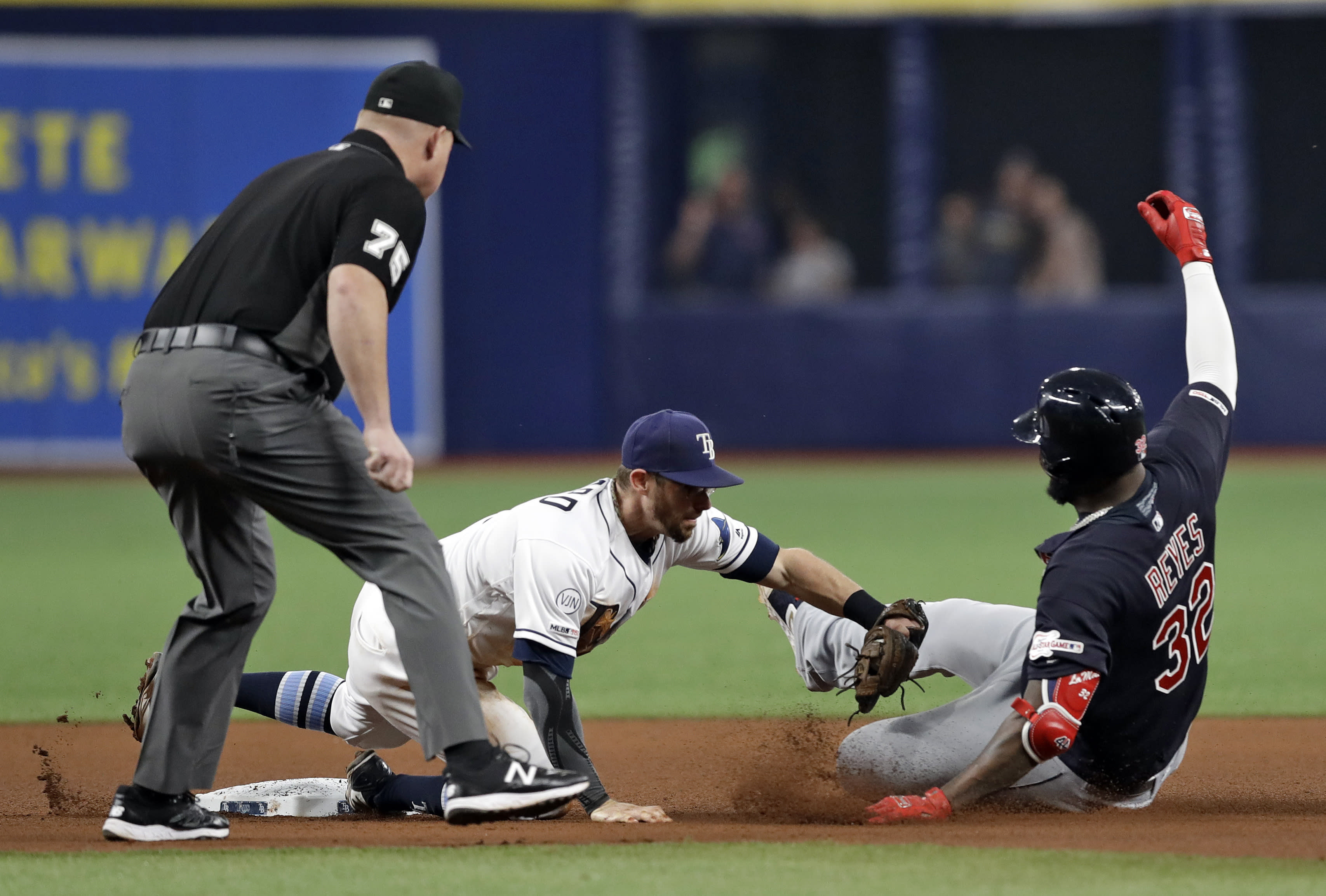 Tampa Bay Rays second baseman Eric Sogard tags out Cleveland Indians' Franmil Reyes (32), who was trying to stretch a single into a double during the fourth inning of a baseball game Saturday, Aug. 31, 2019, in St. Petersburg, Fla. Making the call is umpire Tom Woodring. (AP Photo/Chris O'Meara)