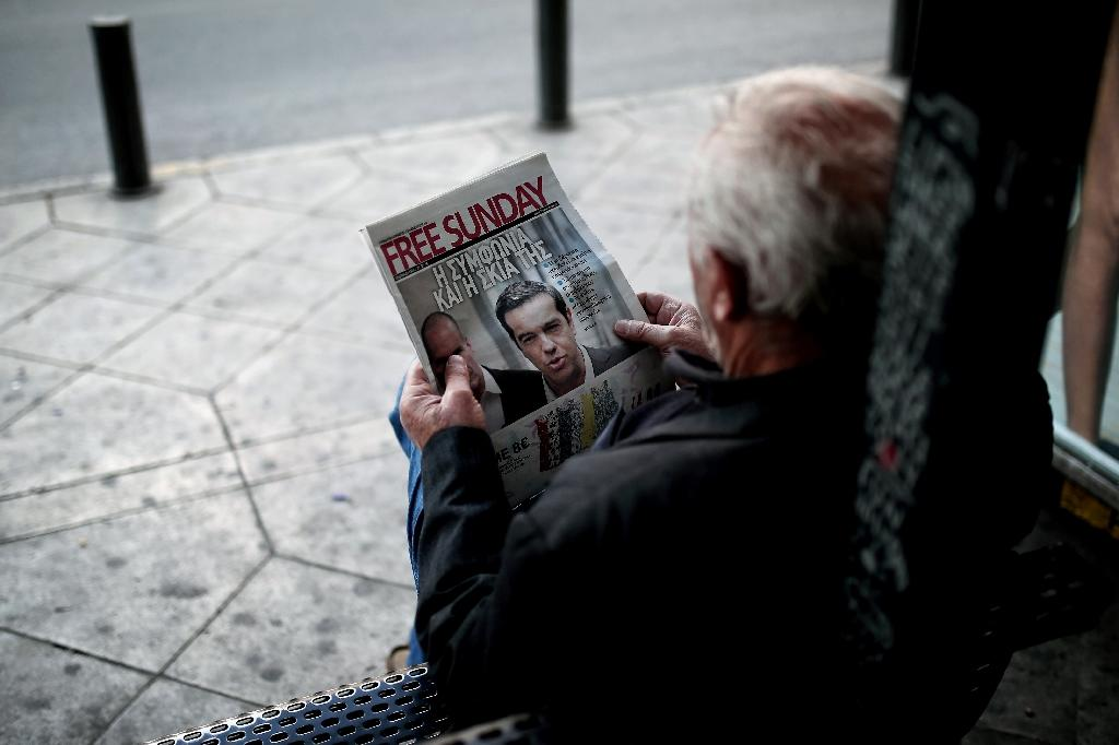 A man sits at a bus station as he reads a newspaper whose front page bears a photograph of Greek Prime Minister Alexis Tsipras in Athens on May 30, 2015 (AFP Photo/Angelos Tzortzinis)