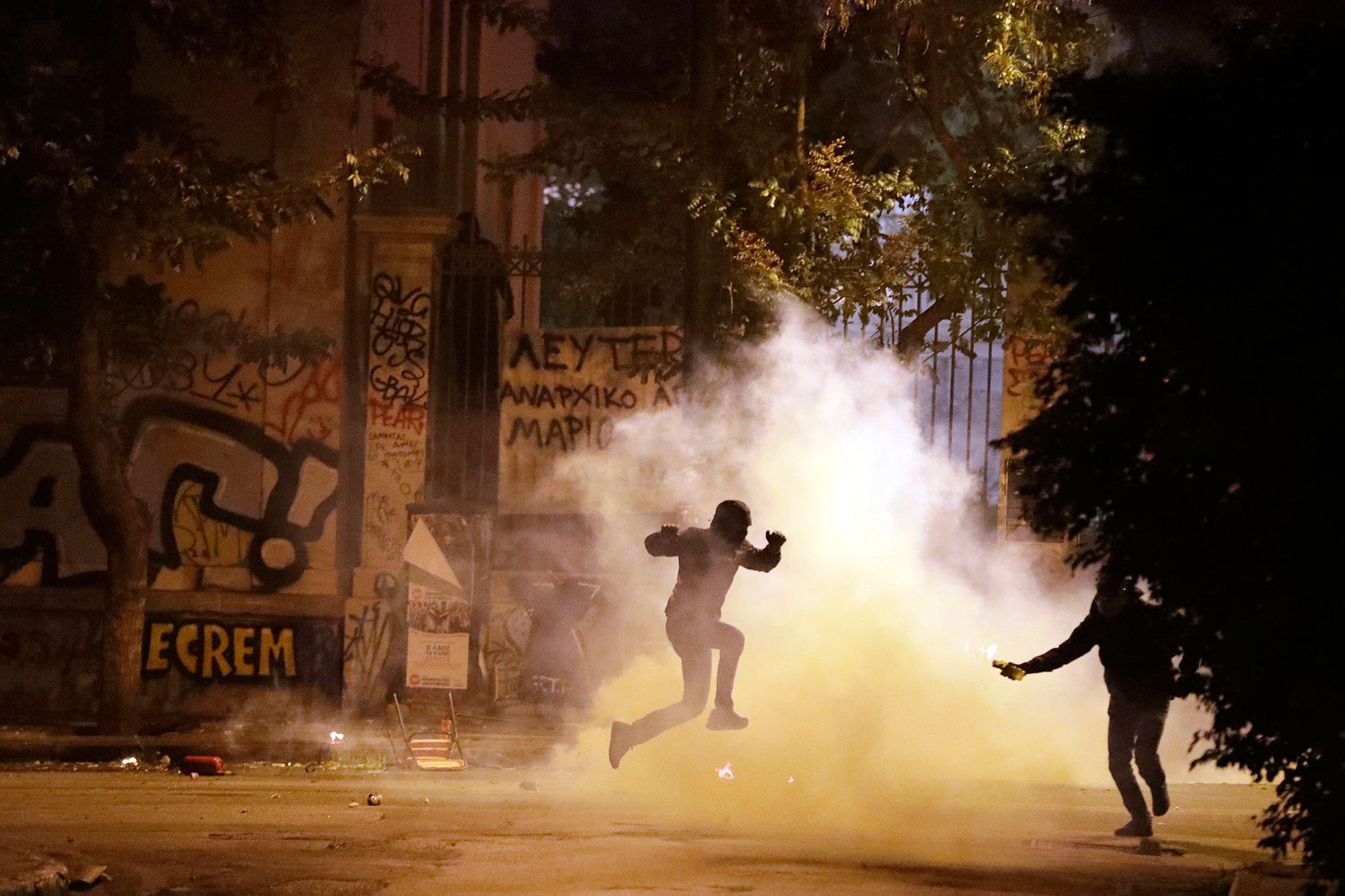 <p>A protester jumps to avoid tear gas as another one prepares to throw a firebomb during a protest against the visit of President Barack Obama in Athens, Tuesday, Nov. 15, 2016. (AP Photo/Thanassis Stavrakis) </p>