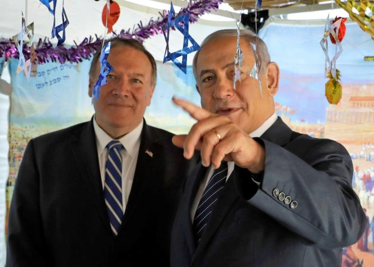 Israeli Prime Minister Benjamin Netanyahu (right) welcomes US Secretary of State Mike Pompeo to a sukkah, a temporary hut constructed to be used during the week-long Jewish festival of Sukkot, in Jerusalem in October 2019 (AFP Photo/Sebastian Scheiner)
