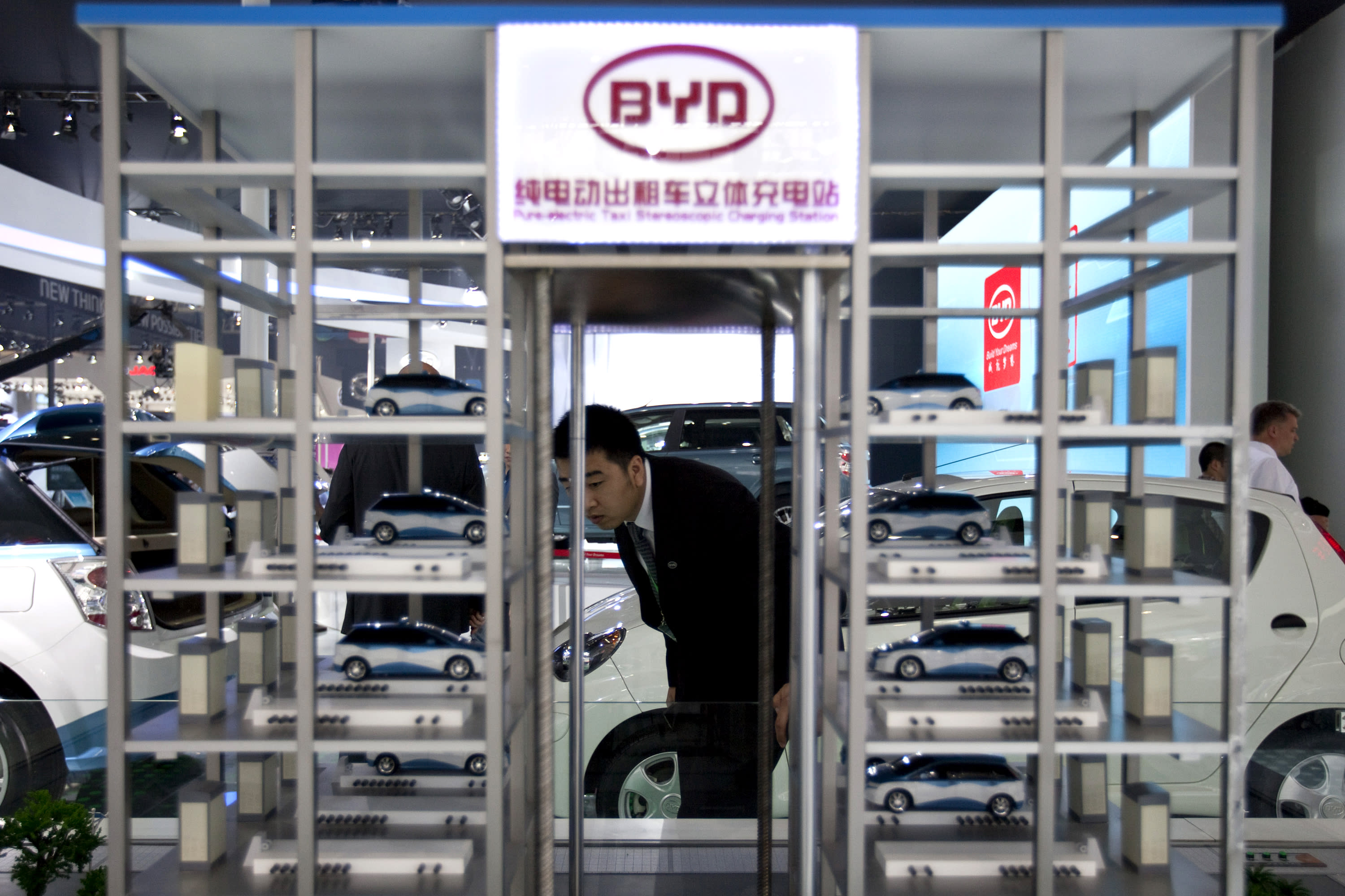 In this Monday April 23, 2012 photo, a BYD employee checks a model of a charging station for BYD's electric taxi cars at 2012 Beijing International Automotive Exhibition in Beijing, China. China's most advanced developer, BYD Co., in which American investor Warren Buffett's Berkshire Hathaway Corp. owns a 10 percent stake, says its electric e6 sedan can travel 300 kilometers (190 miles) on a charge, similar to Western models. (AP Photo/Alexander F. Yuan)