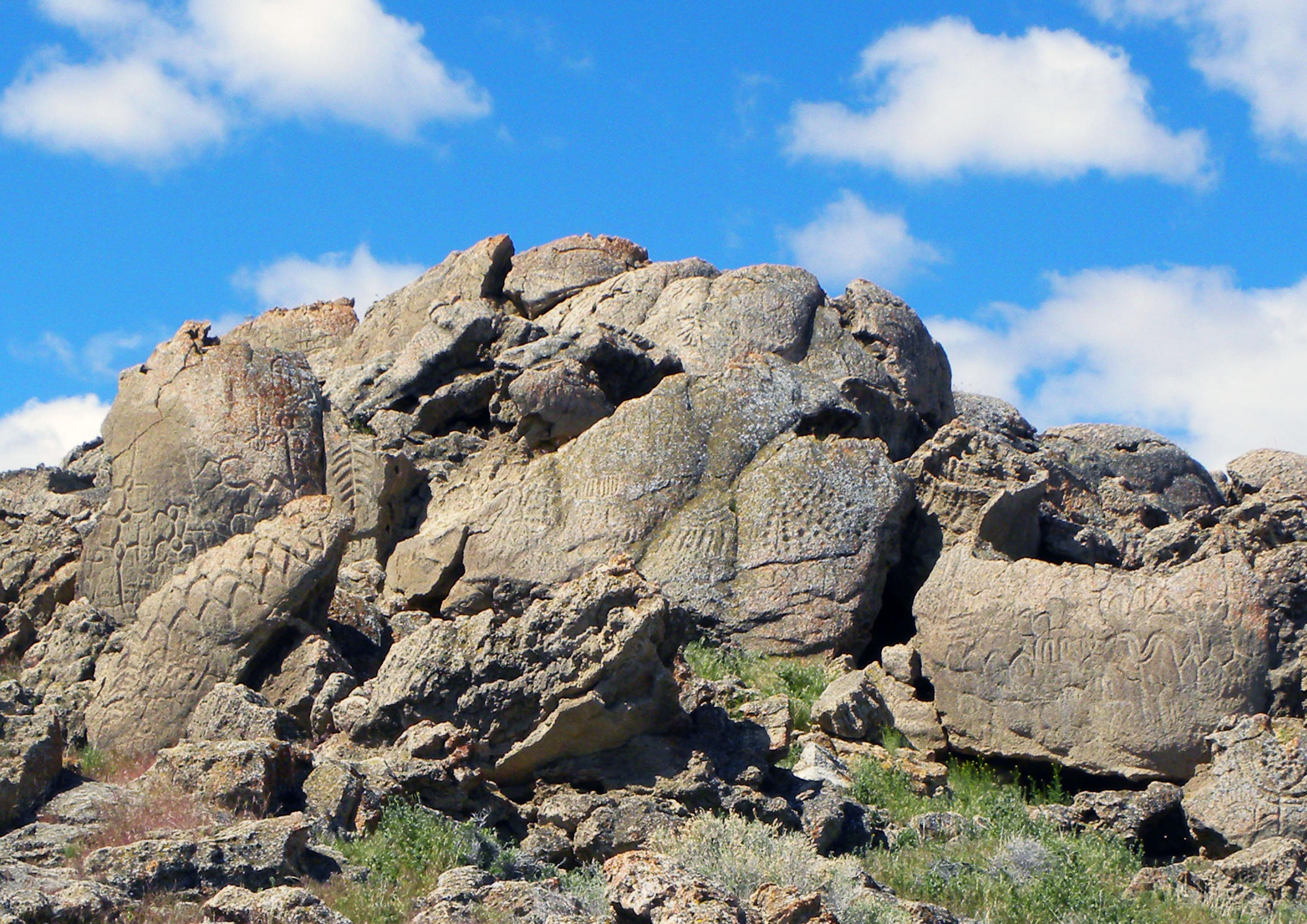 This May 2012 photo provided by the Nevada State Museum shows ancient carvings on limestone boulders near Nevada's Pyramid Lake which have been confirmed to be the oldest recorded petroglyphs in North America - at least 10,500 years old. Larry Benson, the curator of anthropology at the University of Colorado Natural History Museum, and Eugene Hattori, curator of anthropology at the Nevada State Museum, were among the co-authors of a paper on the findings published August 2013 in the Journal of Archaeological Science. This site was once the shoreline of the now dried up Winnemucca Lake. (AP Photo/Nevada State Museum, Eugene Hattori)