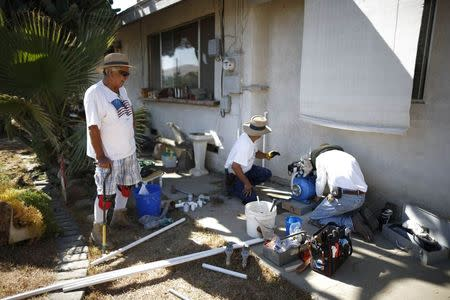 Manuel Rodriguez, 83, (L) watches as workmen install a water pump to carry water from an outdoor container into his home in Porterville, California October 14, 2014.REUTERS/Lucy Nicholson