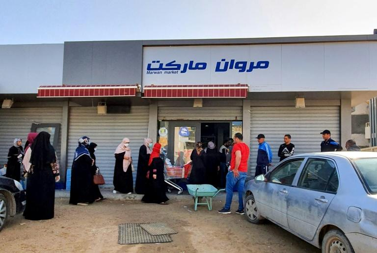 Libyans queue outside a supermarket in Tripoli as a lockdown restricts shopping hours in the capital (AFP Photo/Mahmud TURKIA)