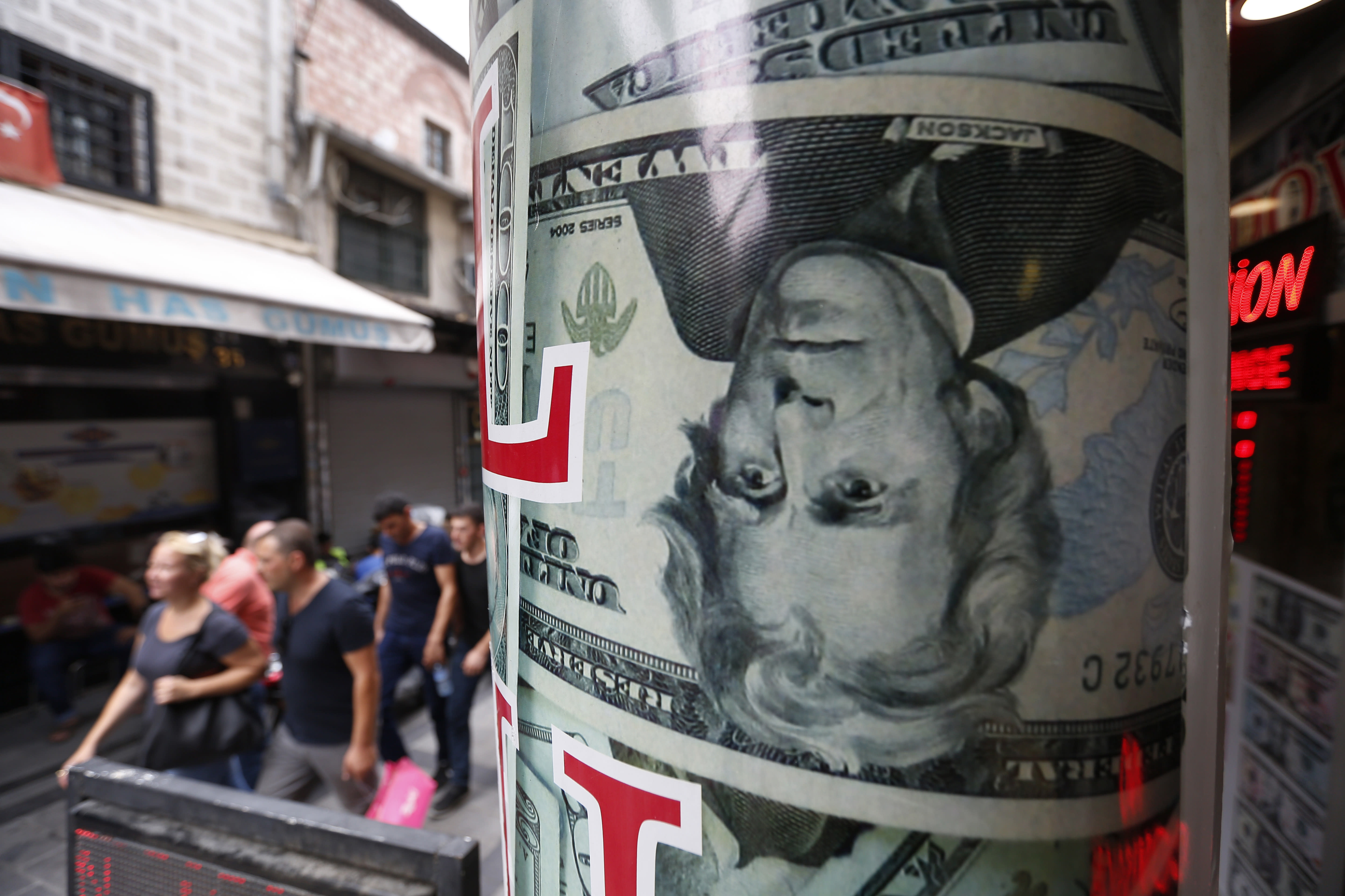 People walk past a currency exchange shop in Istanbul, Friday, Aug. 17, 2018. Turkey's lira currency fell once again, as Turkey and the United States exchanged new threats of sanctions Friday, keeping alive a diplomatic and financial crisis. (AP Photo/Lefteris Pitarakis)