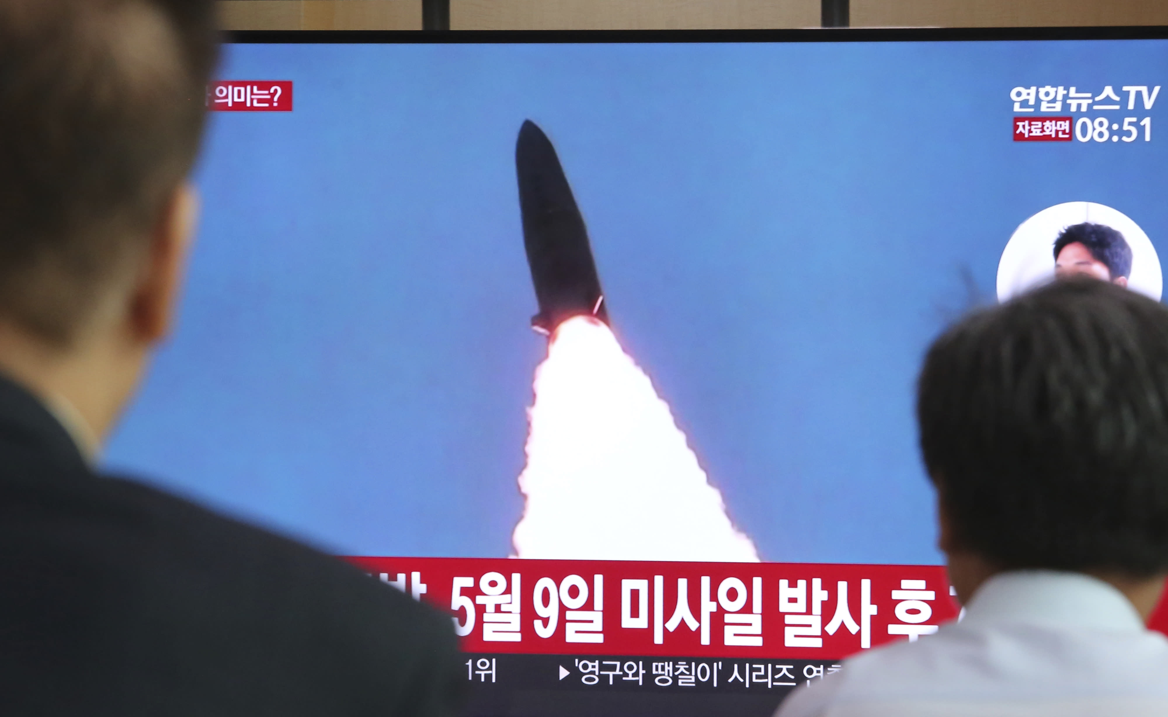"""People watch a TV showing a file image of North Korea's missile launch during a news program at the Seoul Railway Station in Seoul, South Korea, Thursday, July 25, 2019. North Korea fired two unidentified projectiles into the sea on Thursday, South Korea's military said, the first launches in more than two months as North Korean and U.S. officials work to restart nuclear diplomacy. The signs read: """"North Korea fired after May 9."""" (AP Photo/Ahn Young-joon)"""