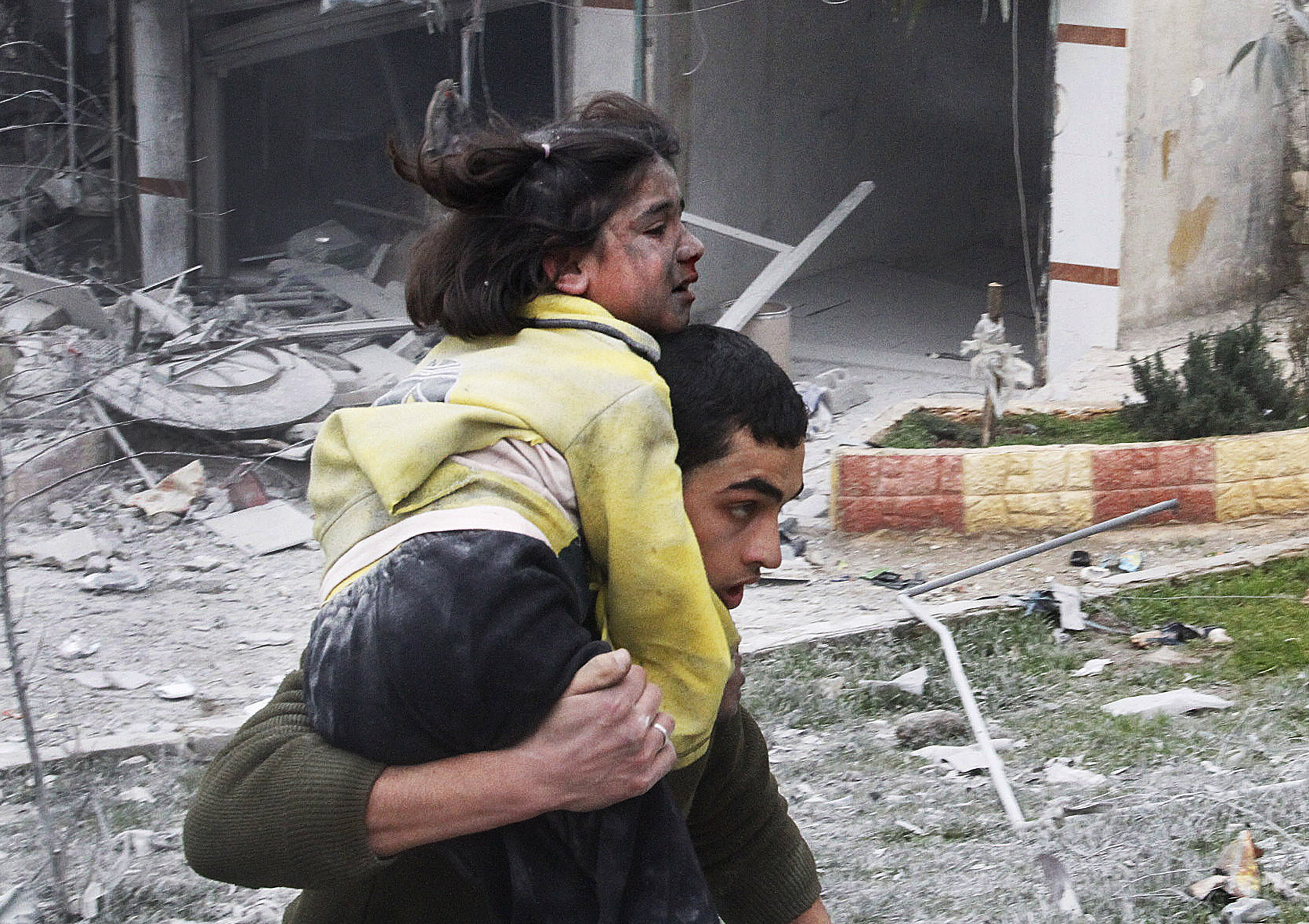 Syrian man carries his sister who was wounded in a government airstrike hit the neighborhood of Ansari, in Aleppo, Syria, Sunday, Feb. 3, 2013. The Britain-based activist group Syrian Observatory for Human Rights, which opposes the regime, said government troops bombarded a building in Aleppo's rebel-held neighborhood of Eastern Ansari that killed over 10 people, including at least five children. (AP Photo/Abdullah al-Yassin)
