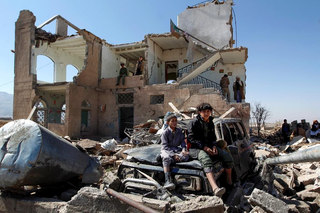 Children sit amidst the rubble of a house hit by Saudi-led coalition air strikes on the outskirts of the Yemeni capital Sanaa on November 14, 2016 (AFP Photo/Mohammed Huwais)