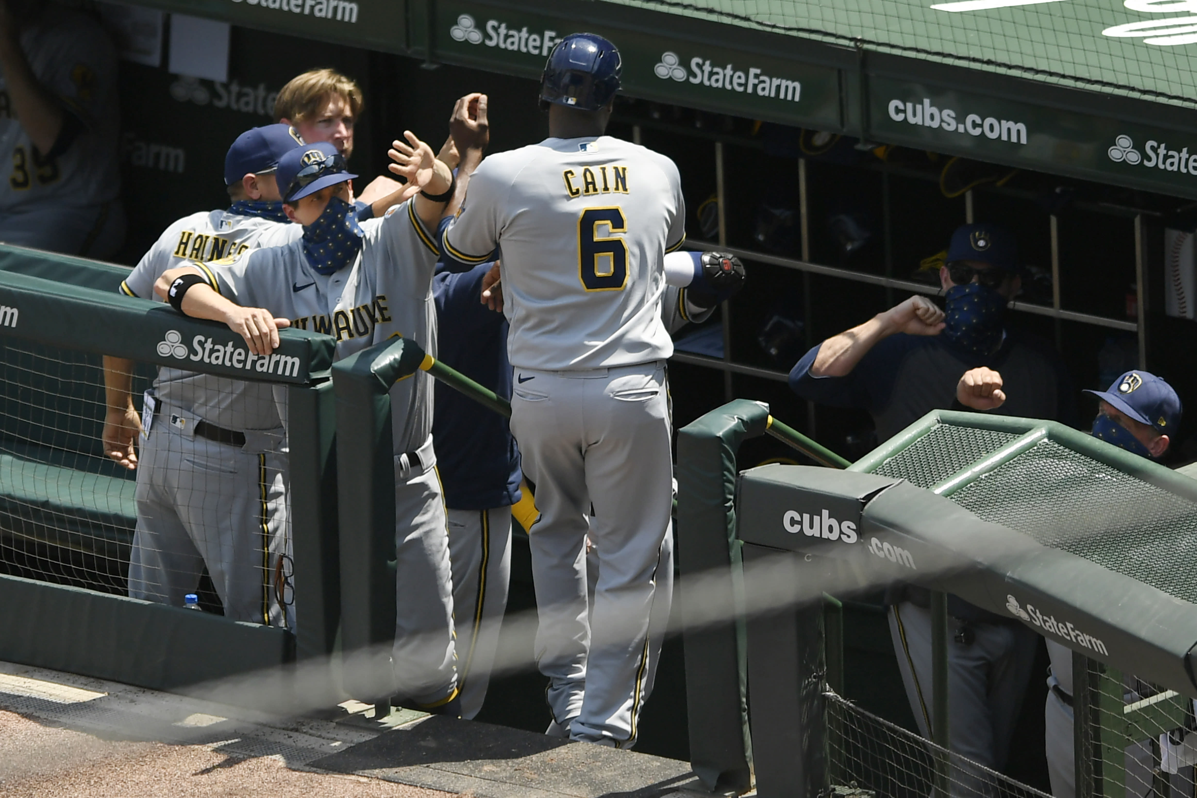 Milwaukee Brewers manager Craig Counsell left, celebrates with Lorenzo Cain (6) after he scored one a Eric Sogard single during the second inning of a baseball game against the Chicago Cubs Saturday, July 25, 2020, in Chicago. (AP Photo/Paul Beaty)
