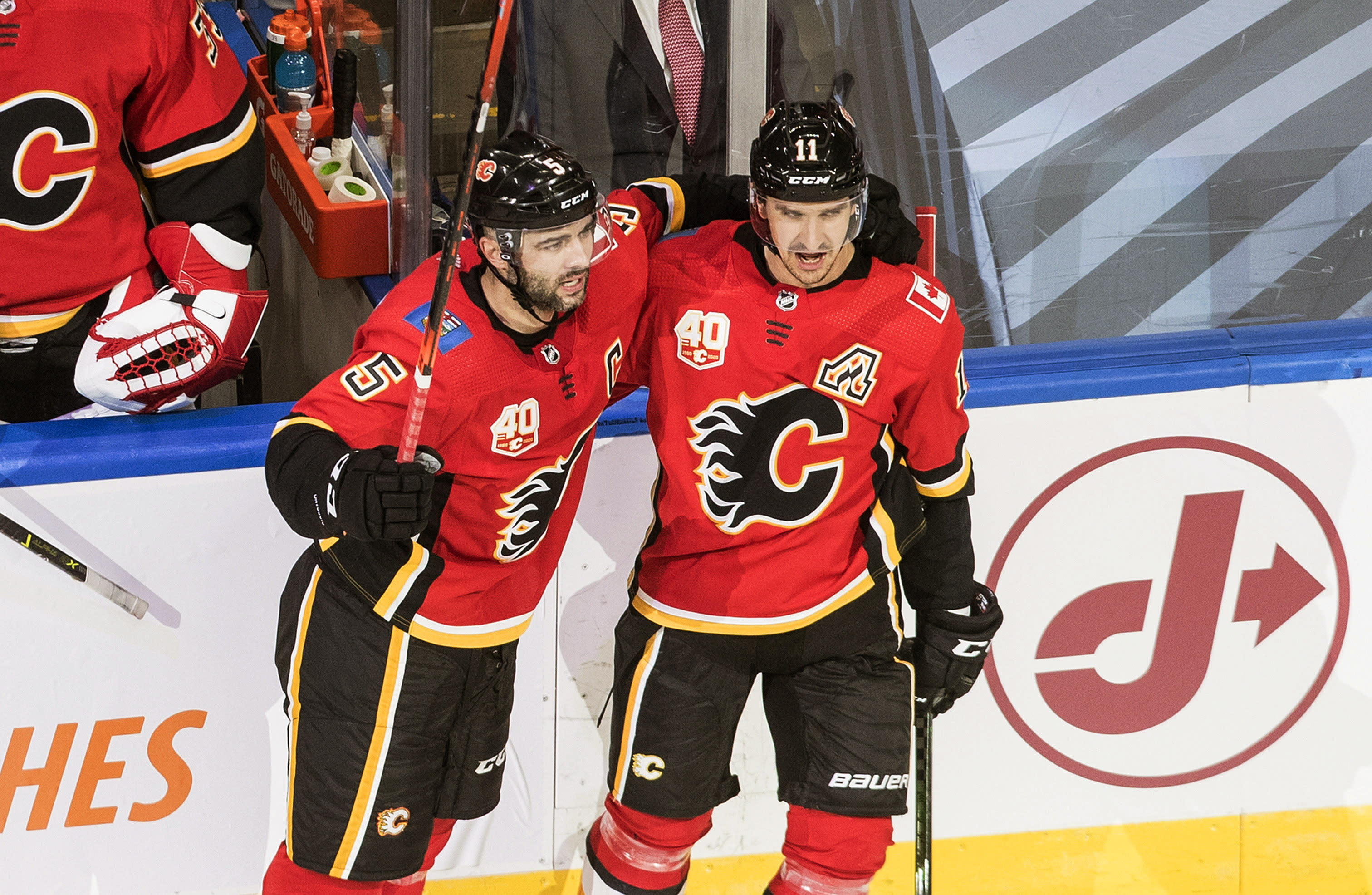 Calgary Flames' Mark Giordano (5) and Mikael Backlund (11) celebrate a goal against the Winnipeg Jets during the second period of an NHL hockey playoff game Saturday, Aug. 1, 2020 in Edmonton, Alberta. (Jason Franson/The Canadian Press via AP)