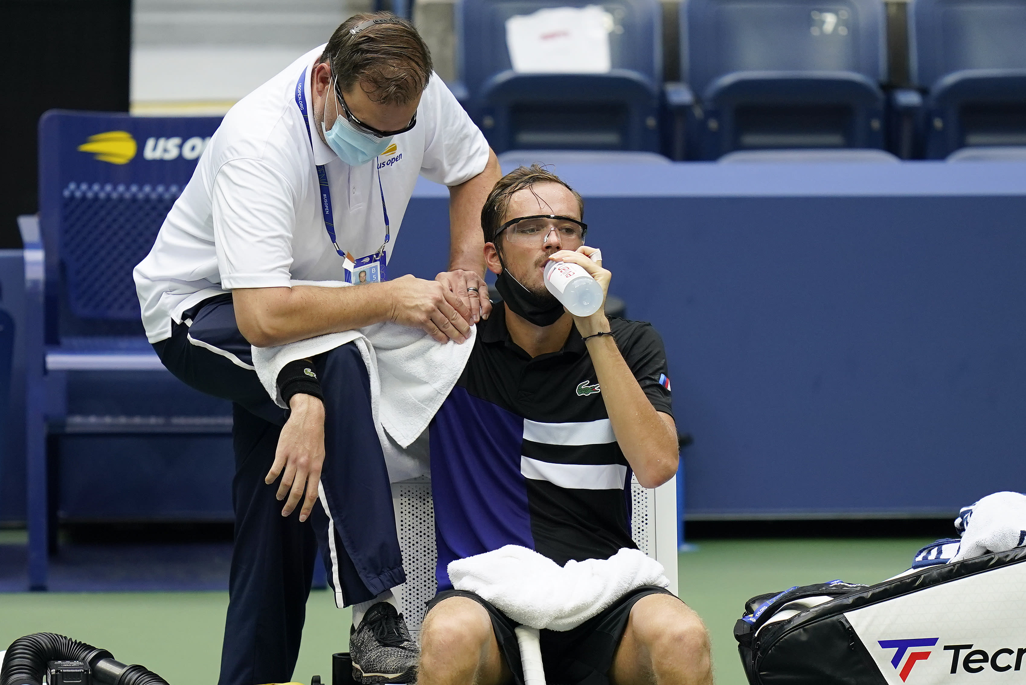 A trainer works on the shoulder of Daniil Medvedev, of Russia, during the quarterfinals of the US Open tennis championships against Andrey Rublev, of Russia, Wednesday, Sept. 9, 2020, in New York. (AP Photo/Seth Wenig)