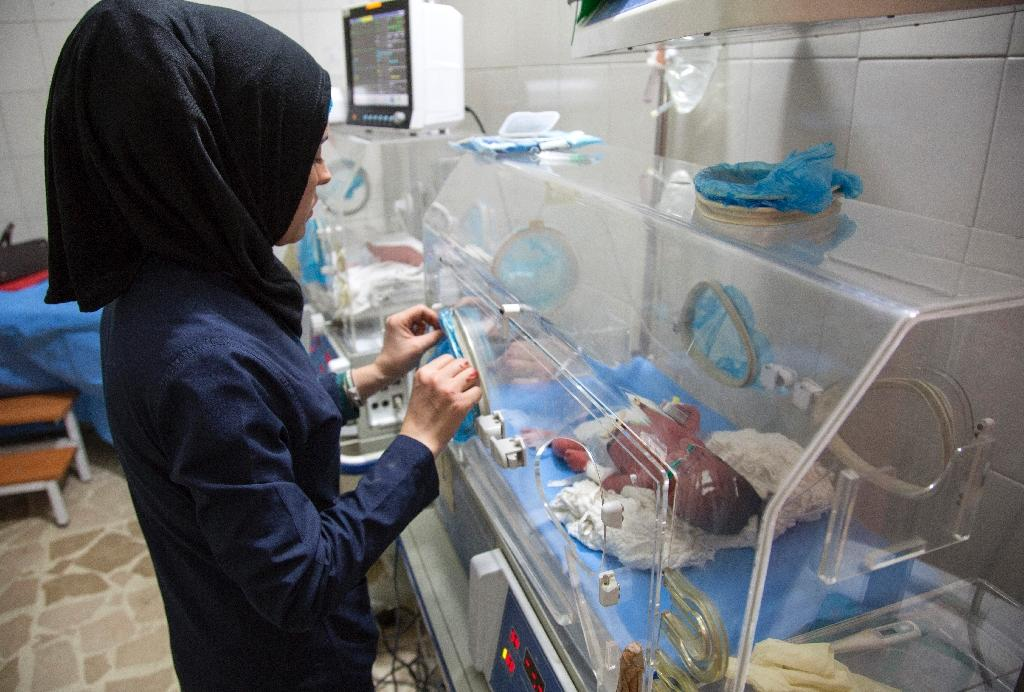 This file picture shows a Syrian nurse standing next to incubators with newborns at a children's hospital on June 9, 2016